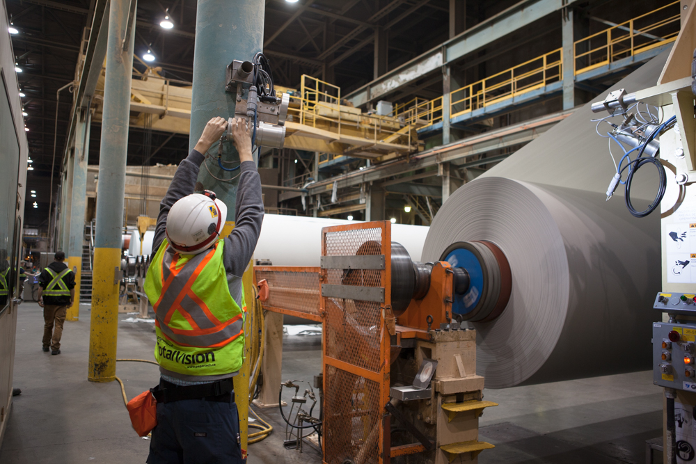 A service technician installs a Papertech WebVision camera in a paper mill.